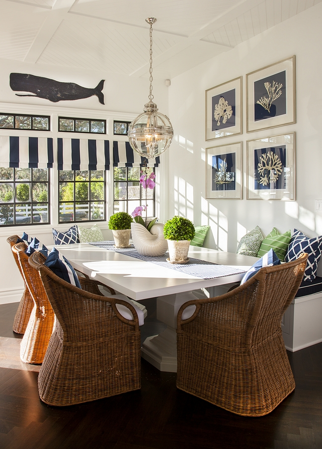 Coastal Breakfast nook Coastal Breakfast nook with wicker dining chairs and a white dining table complemented by a custom banquette Coastal Homes Coastal Interior Design #coastalbreakfastnook #coastalhomes #coastalinteriors #banquette #whitediningtable #wickerdiningchair