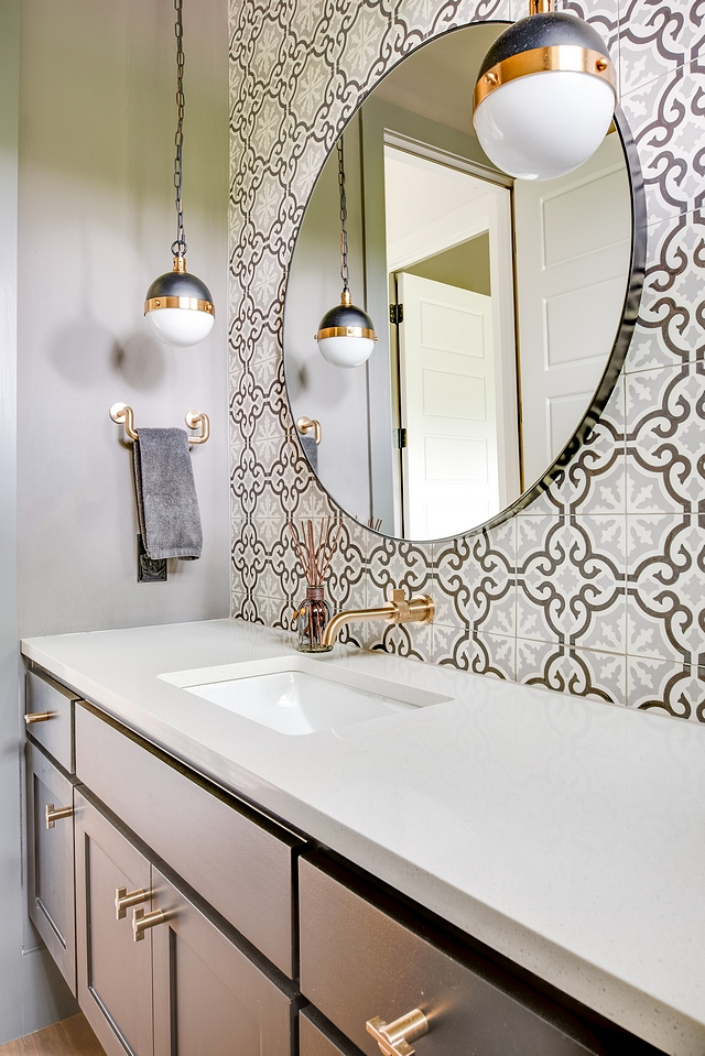 Powder room features a custom grey floating vanity, charcoal gray and light gray cement tile as an accent wall and globe mini-pendants #powderroom #bathroom #cementtile #floatingvanity