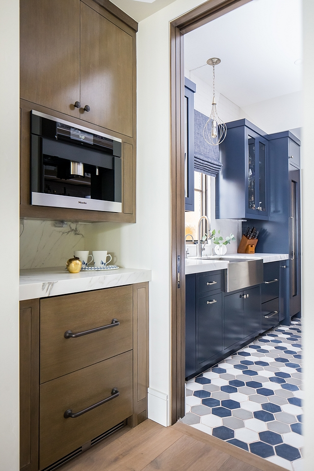 The kitchen leads to a coffee bar and fully-equipped pantry with navy blue cabinets in Benjamin Moore Hale Navy HC154 #pantry #kitchen #coffeebar #coffeebarcabinet #barcabinet #bar #navybluecabinet #BenjaminMooreHaleNavy #BenjaminMooreHC154