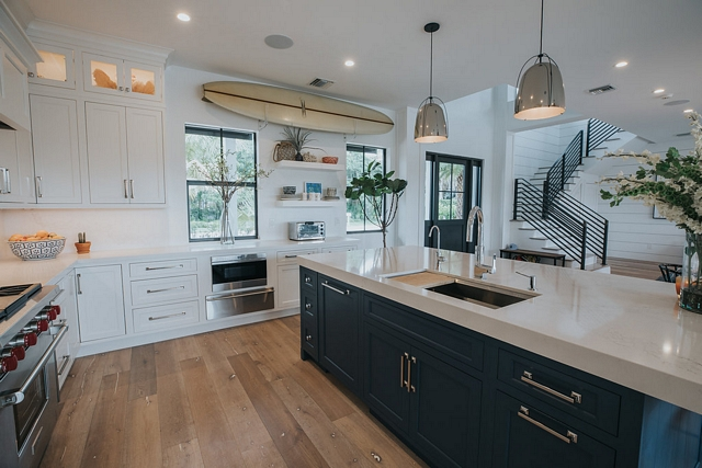Coastal kitchen A surfboard graces the wall showing the love of surf enjoyed in this home #coastalkicthen #surfboard