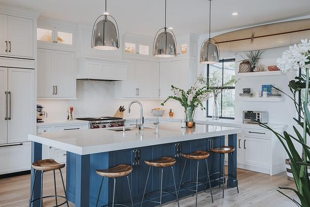 This coastal inspired home features a denim blue island as the focal point of the contrasting white kitchen #coastalkitchen #blueandwhitekitchen #kitchen #homedecor #coastalhomes