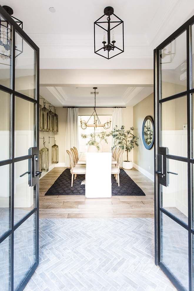 Black metal and glass French doors open to a foyer with herringbone brick flooring with direct view of a neutral dining room