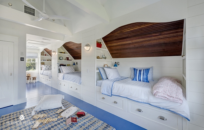 Low ceiling Bunk Room The built-in bunk beds features a shipshape style with mahogany ceilings, white shiplap side walls, and nautical bed linens and accents