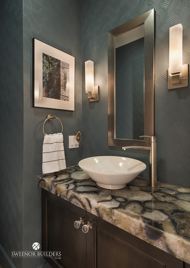 The powder room's countertop is a 3-inch-thick agate and quartz. Walls are covered in a paintable wallpaper in Night Rendezvous by Olympic Paint