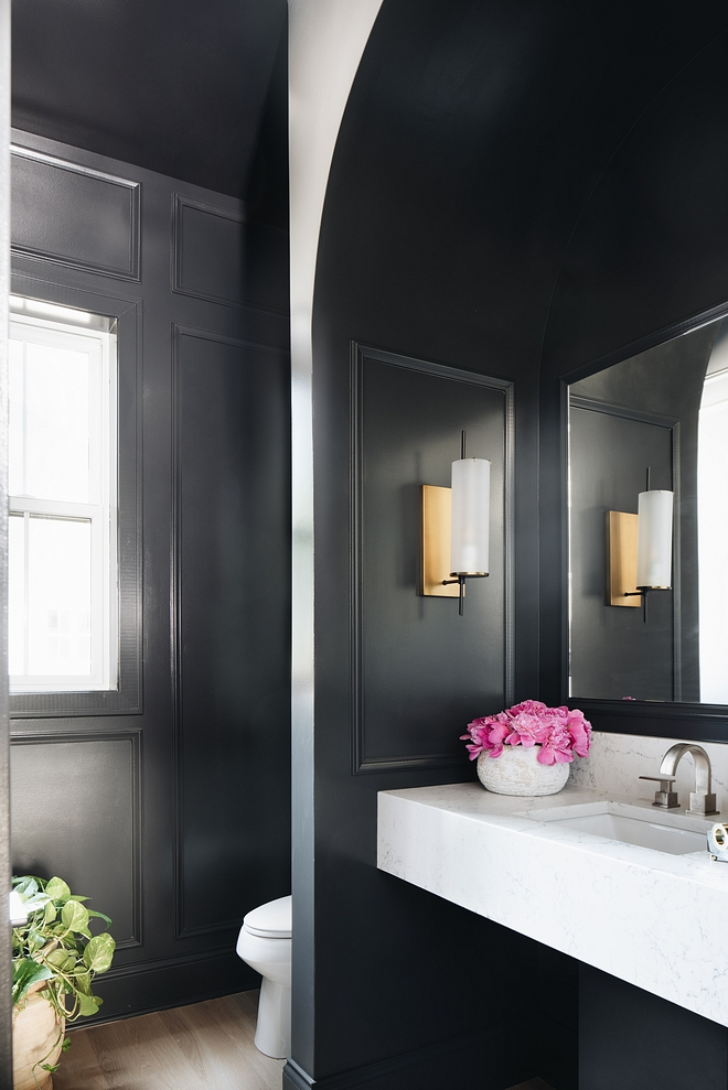 This powder room features black paneled walls, painted in Benjamin Moore Wrought Iron 2124-10, and a marble-looking floating vanity