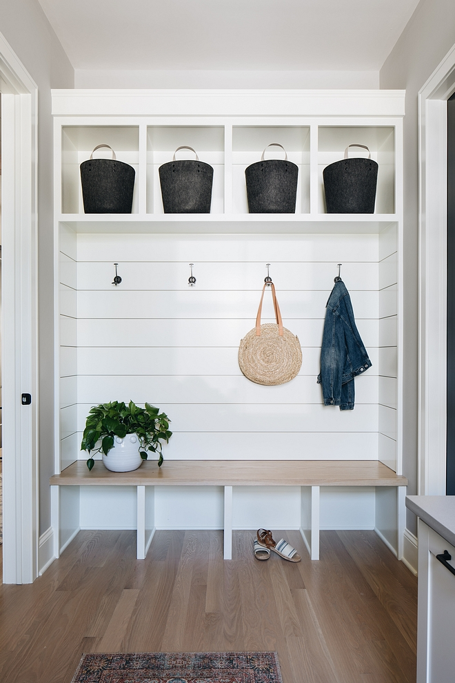 The mudroom features shiplap and custom cabinetry with White Oak seat