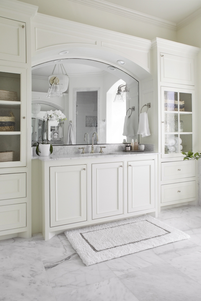 Bathroom cabinets feature a warm white color, Benjamin Moore Swiss Coffee, and doors with seeded glass
