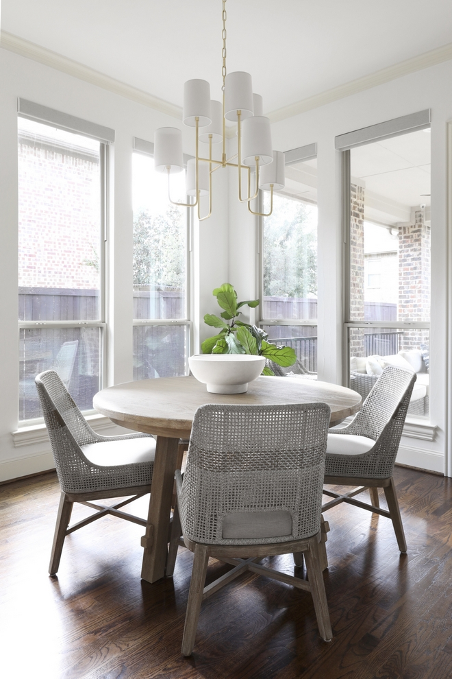 Breakfast Room Windows bring in plenty of natural light and a round dining table eases the flow between the kitchen and the back porch