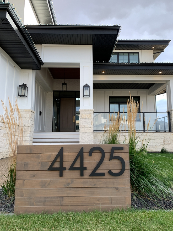 The exterior of this gorgeous home is complemented by a Mid-century inspired address sign with horizontal wood planks and extra large house numbers