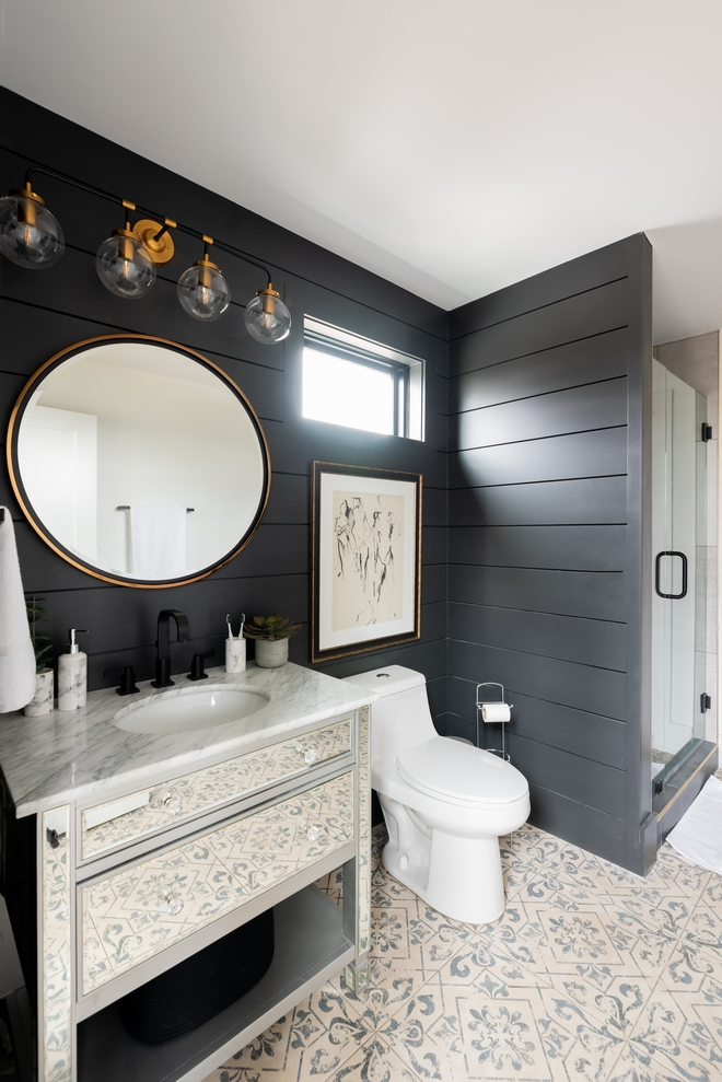 The beautiful and sophisticated Main Bathroom features black Shiplap walls, a mirrored vanity and patterned floor tiles