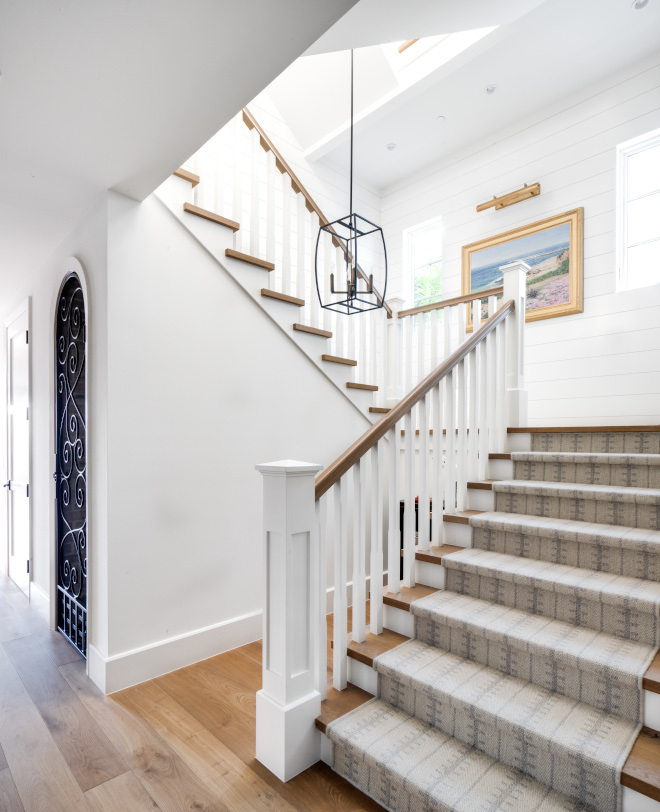 Coastal-Home-Staircase-White-wood-rails-painted-in-Dunn-Edwards-Antique-Paper-Treads-and-railings-are-custom-stained-to-match-hardwood-floors
