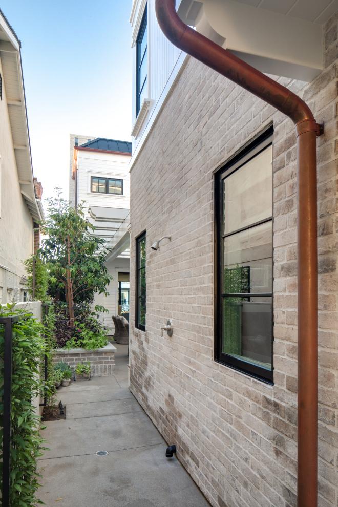 Whitewash-brick-siding-black-windows-copper-gutters-copper-downspouts