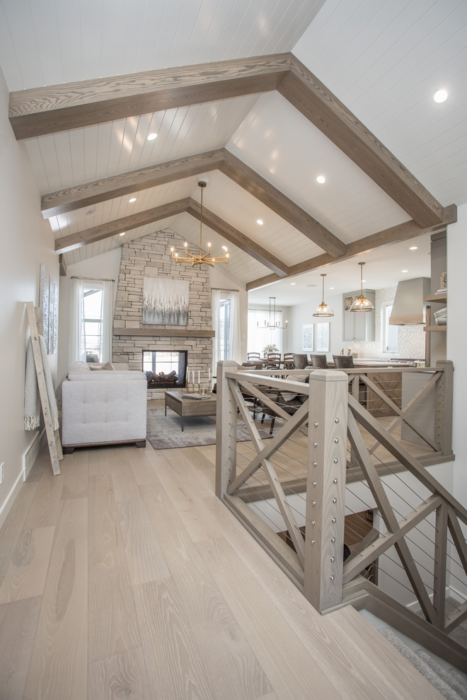 A vaulted ceiling with wood beams and shiplap centered on the double sided stone clad fireplace make this living room the heart of the home #vaultedceiling #woodbeamsshiplapceiling #woodbeams #shiplap #Bemans #doublesidedfireplace #stonefireplace #stonecladfireplace Farmhousestaircase #Xrailing #cablerailing #livingroom