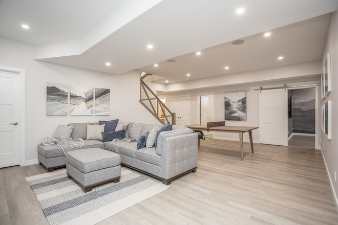 Basement Layout The basement features a large family room and wet bar as well as a theater room enclosed by a sliding barn door #Basement #BasementLayout #familyroom #wetbar #theaterroom #slidingbarndoor #barndoor