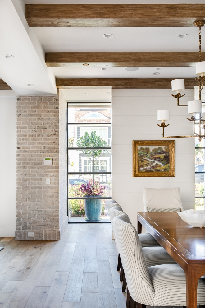 Whitewashed-brick- along-with-a wall-clad-in-shiplap-accentuates-the-Foyer-and-creates-some-privacy-to-the-rest-of-the-house