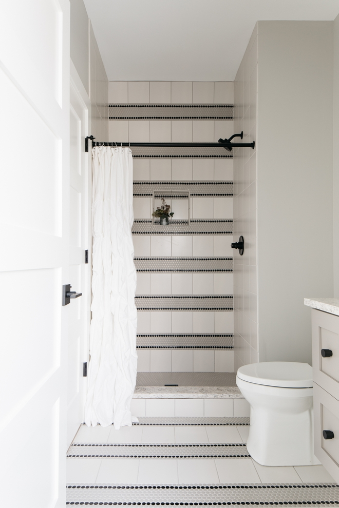 You really don't need to break the bank when designing a child's bathroom and this one is here to show us how it's done. Combine affordable yet timeless tiles and be creative with the design to make the entire room pop and feel authentic Bathroom Tiling: Matte Grey Penny Tile (also applied to the shower pan), Black Matte Penny Tile, 8x8 White Tile