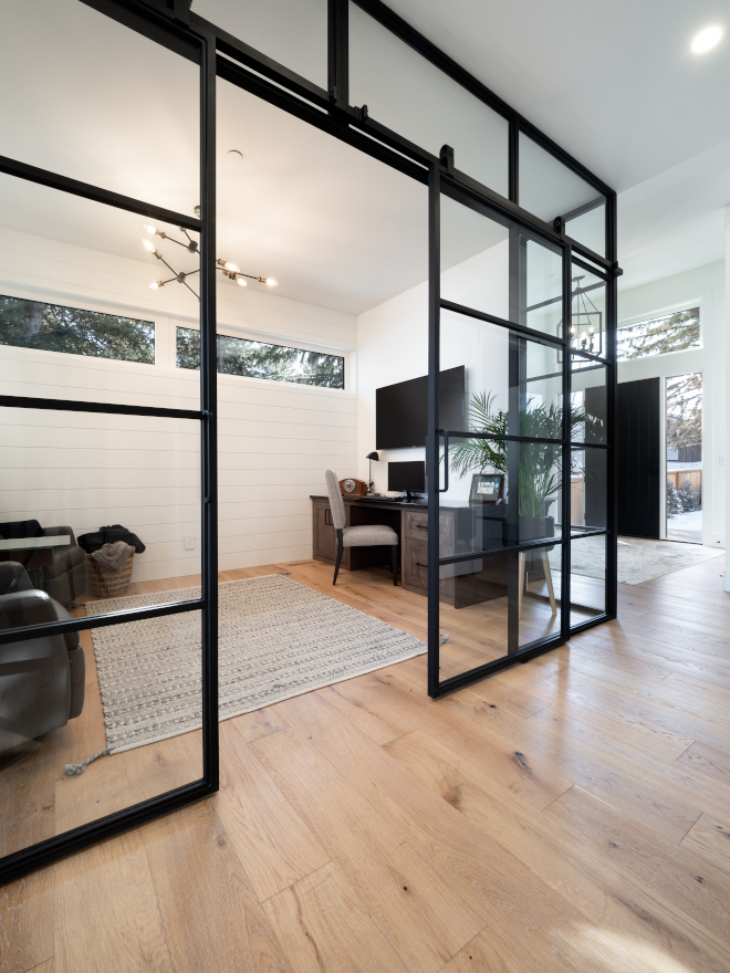 Black iron framed glass encloses the den with sliding double doors and clerestory windows bringing light and views of the treetops without compromising privacy Den #Blackironframedglassencloses #den #slidingdoubledoors #clerestorywindows