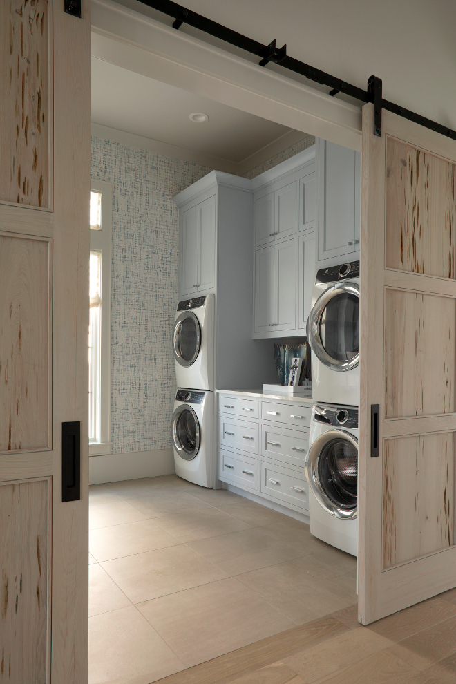 Featuring Pecky Cypress barn doors, blue gray cabinets and two sets of stacked washer and dryers, this beach house Laundry Room would certainly make our lives a little easier #laundryroom #beachouse #twosetswasherdryer #stackedwasheranddryers #barndoor #peckycypress