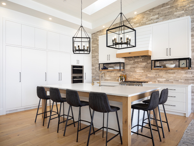 Kitchen Marble stone accents the kitchen wall and is contrasted by simple slab cabinetry with details such as metal open shelves shiplap hood range #Kitchen #Marblestonewall #stoneaccentwall #kitchenwall #slabcabinetry #metalopenshelves #shiplaphood #shiplaphoodrange