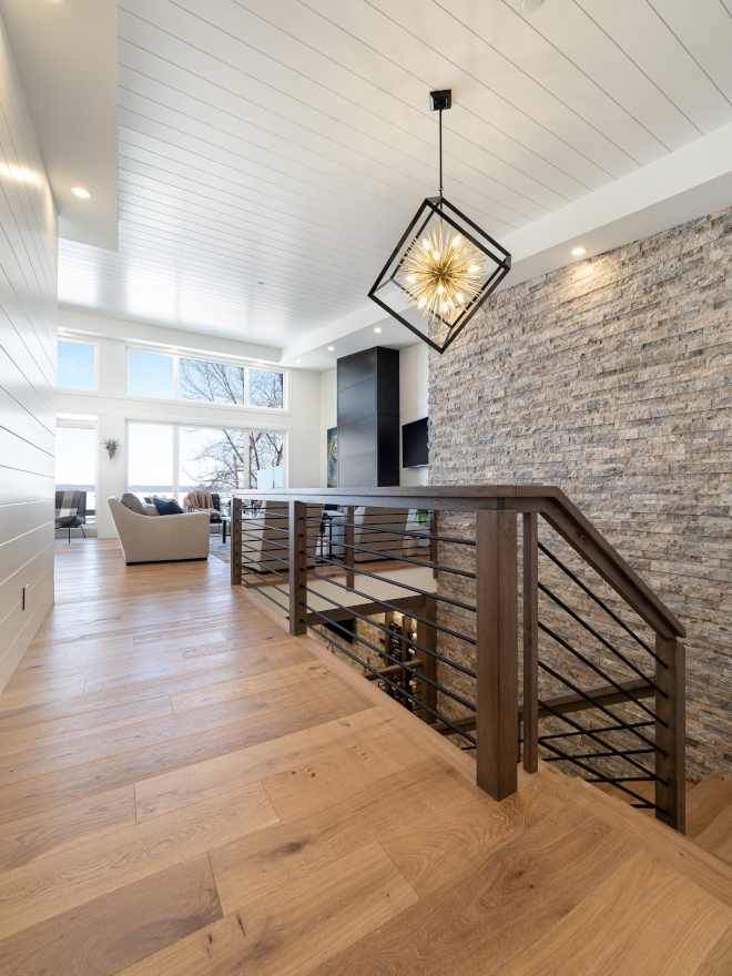 The open stairwell hosts a split Travertine feature wall and unique horizontal steel and wood railing Modern Staicase Modern Home Staircase Modern Farmhouse Staircase #openstairwell #Travertine #horizontalsteel #woodrailing #ModernStaicase #ModernHome #Staircase #ModernFarmhouse #ModernStaircase