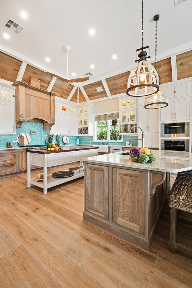 The kitchen features white inset upper cabinetry balanced with rustic Hickory base cabinets with a driftwood feel. The driftwood V-groove ceiling is framed in white beams and the two islands offer a great work space as well as an island for socializing