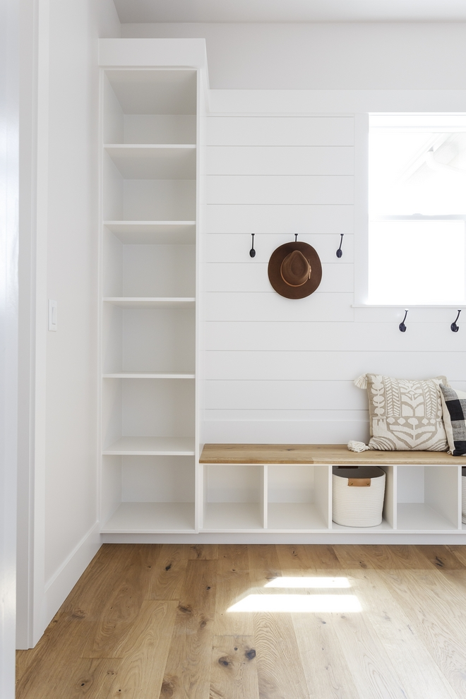 The mudroom bench features hardwood top. Shiplap paneling accentuates the mudroom back wall. Cabinetry and shiplap are in Sherwin Williams Snowbound