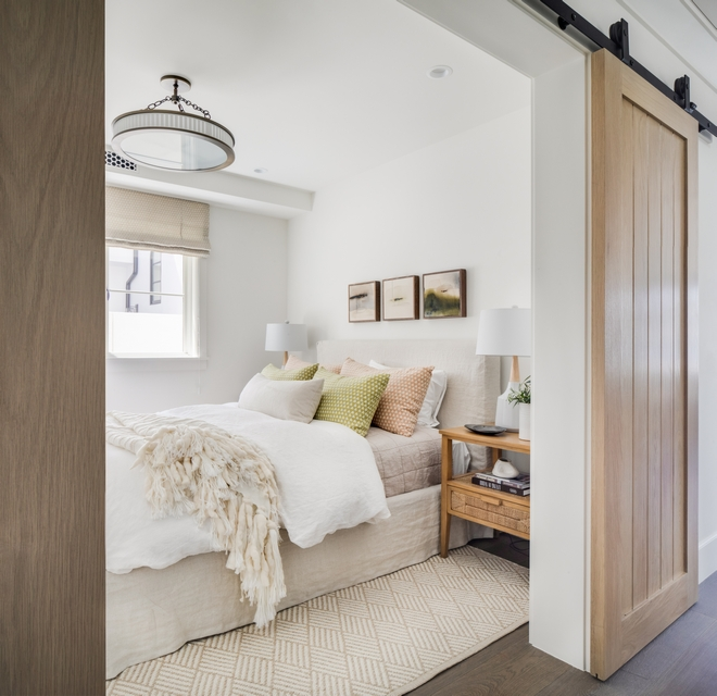 White Oak Barn Door conceal a Guest Bedroom with white walls and natural linen slipcovered bed White Oak Barn Door conceal a Guest Bedroom with white walls and natural linen slipcovered bed #WhiteOak #BarnDoor #Bedroom #whitewalls #naturallinen #linenbed #slipcoveredbed