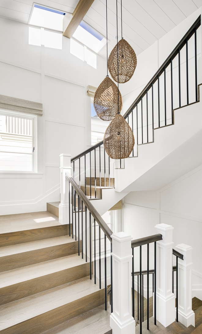 Staircase Stairs Waterfall staircase tread staircase features rope pendants hung in different heights and waterfall-style White Oak tread Walls are clad in full-height simple shaker paneling in Dunn-Edwards Whisper White #Staircase #Stairs #Waterfallstaircasethread #staircasetread #ropependant #WhiteOak #tread #shakerpaneling