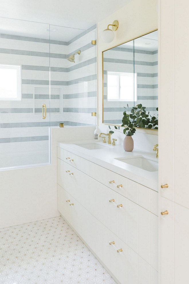 Vertical plank cabinetry and striped shower tiles add plenty of interest to this newly-renovated bathroom #Verticalplankcabinetry #plankcabinetry #stripedshower #showertile #bathroom