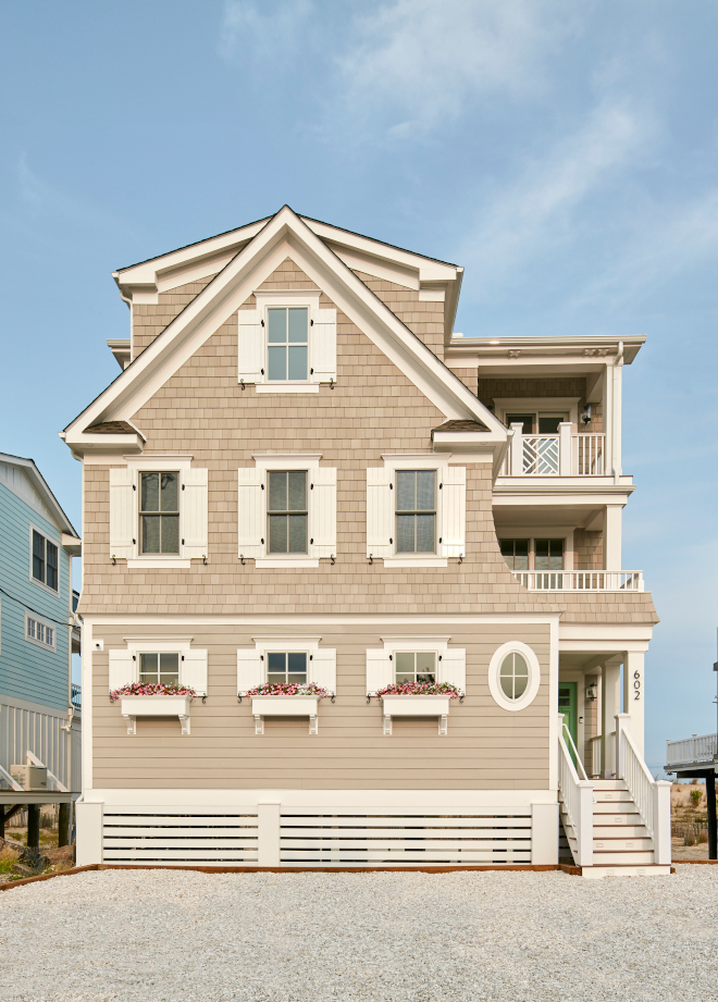 Beach House Outside the home the unique exterior design is accentuated by Sherwin Williams Worldly Gray siding with a bright front door and charming window boxes #BeachHouse #home #uniqueexterior #exterior #exteriordesign #SherwinWilliamsWorldlyGray #siding #frontdoor #windowboxes