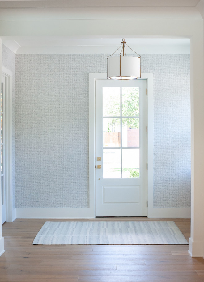 Unique wallpaper by Thibaut greets you as you step into the foyer Though it appears as if it's grasscloth the wall is smooth with the appearance of subtle texture highlighted by the beautiful natural light that streams into the foyer #foyer #wallpaper #Thibaut #grasscloth #texture #naturallight