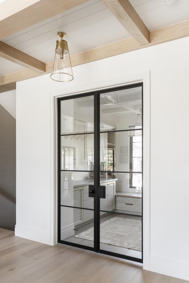 The main home office is concealed by custom black metal and glass doors and it features plenty of built-ins #homeoffice #customdoor #metaldoor #glassandmetaldoor