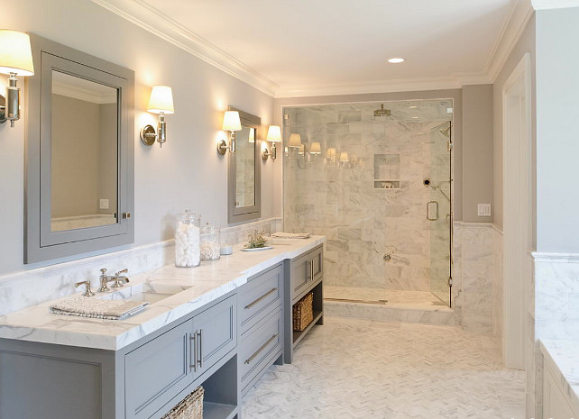 Gray Bathroom cabinet. Gray Bathroom cabinet paint color. Gray bathroom features gray double washstand paired with statuary marble countertop and his and her sinks and gray medicine cabinets over herringbone marble tiled floor. #Bathroom #Gray #Cabinet Blue Water Home Builders.