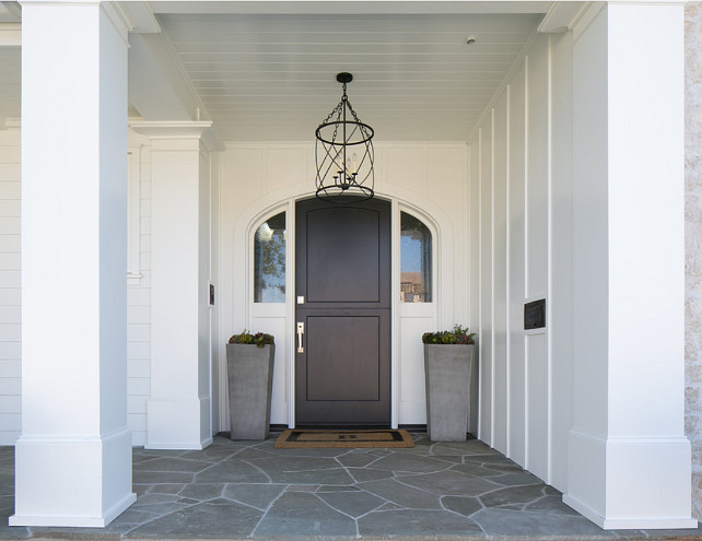 Front Door. Front entry with black front door, stone porch, white exterior and modern planters from Restoration Hardware. Front door lantern. #FrontEntry #FrontDoor #WhiteExterior #Planters #FrontDoorLighting #Lantern