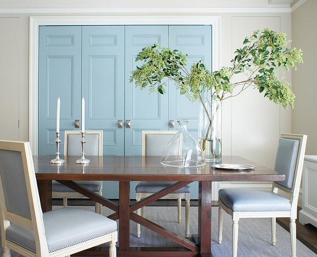 Blue Dining Room. Blue Dining Room Design Ideas. Blue dining room boasts a trestle dining table surrounded by blue French dining chairs with nailhead atop a gray rug and blue doors. #DiningRoom #BlueDiningRoom Christopher Burns