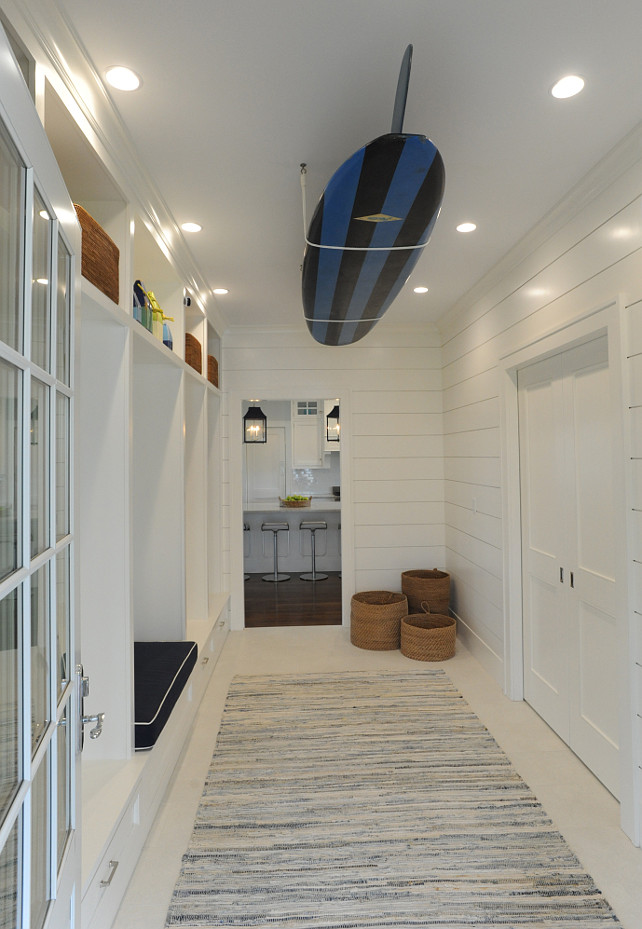 Mudroom. Coastal Mudroom. Coastal Mud Room Ideas. Beach mud room with wall length, built-in lockers featuring a built-in storage bench with overhead cubbies alongside wood planked walls with a ceiling mount surfboard over ivory floors layered with a gray rag rug. #Mudroom #Coastal  Nina Liddle Design.