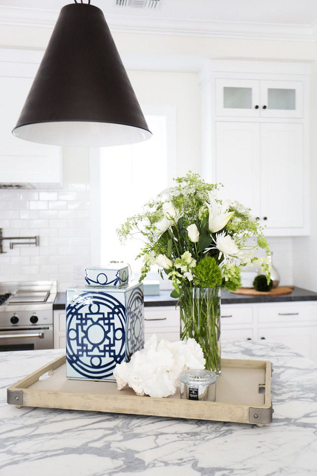 Kitchen Ideas. Stunning kitchen features a Goodman Hanging Lamp illuminating a grey and white marble top island and a wood tray with metal brackets. A white kitchen hood, flanked by windows, stands over a white brick tiled backsplash and a stainless steel stove. The countertop is Carrara Marble. #Kitchen #KitchenIdeas