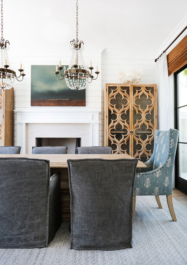 Dining Room Design. This gorgeous dining room features a pair of Paris flea market chandeliers over a wood dining table lined with charcoal gray slipcovered dining chairs as well as blue wingback dining chairs. You will also notice the shiplap accent wall and fireplace flanked by quatrefoil glass cabinets. The glass and steel doors are dressed in bamboo roman shades and white linen draperies. #DiningRoom