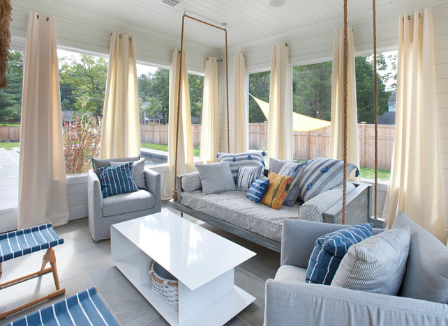 Screened in Porch with Curtains. Porch with Curtains & Swing. Screened-in porch featuring shiplap siding and ceiling, curtains, heated flooring and interchangeable glass and screens, and access to the pool area. #ScreenedinPorch #Curtain Blue Water Home Builders.