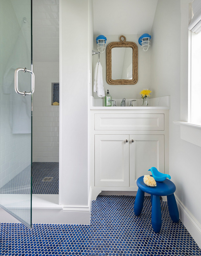 Cottage Kids Bathroom. This cottage kid's bathroom features a white washstand under a Two's Company Know Your Ropes wall mirror and white and blue cage sconces. The walk-in shower has sloped ceiling tiled with white subway tiled and a blue hex tiled shower floor. #Kids #bathroom #Cottage Digs Design Company.