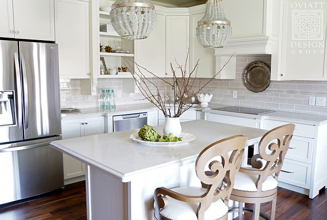 Small Kitchen Reno. The cabinet color is Restoration Hardware Cloud White and the wall color is 1/2 strength BM Edgecomb Gray.  A pair of gray beaded chandeliers hangs over a small kitchen island lined with Noir Saragossa Swivel Stools. Creamy white shaker cabinets are paired with ivory quartz countertops and a gray stacked tile backsplash. A corner kitchen sink is flanked by a dishwasher to the left and an induction cooktop to the right. #Kitchen #KItchenREno #Reno #KitchenProject Oviatt Design Group.