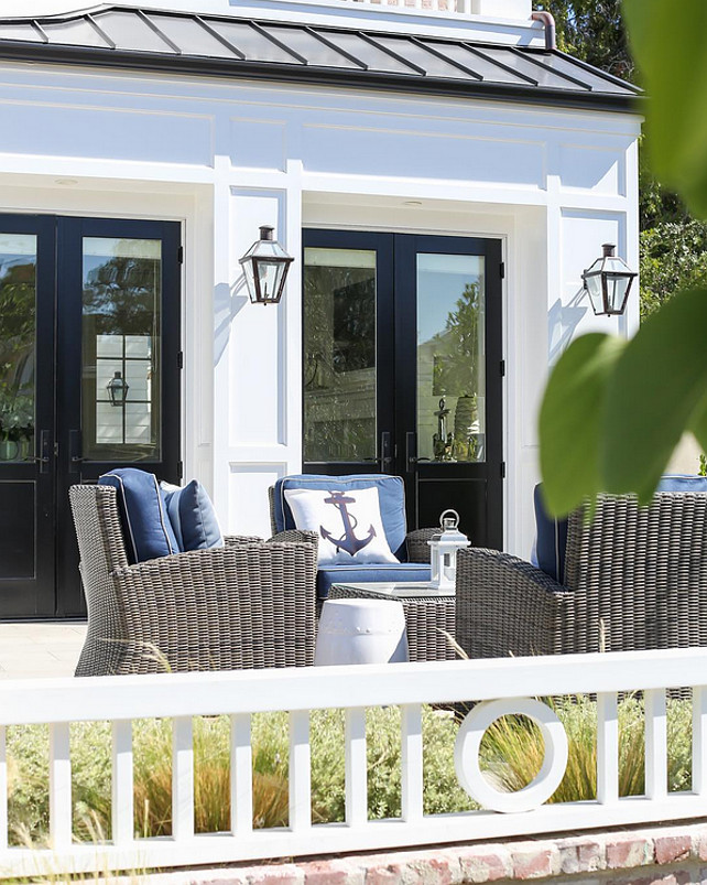 Patio Decorating Ideas. Coastal Patio Decorating Ideas. Beautiful patio with wicker furniture, navy blue cushions to coordinate with the anchor pillows. #patio #Furniture #Coastal #CoastalDecor Brandon Architects. Ryan Garvin photographer. Patterson Custom Homes.