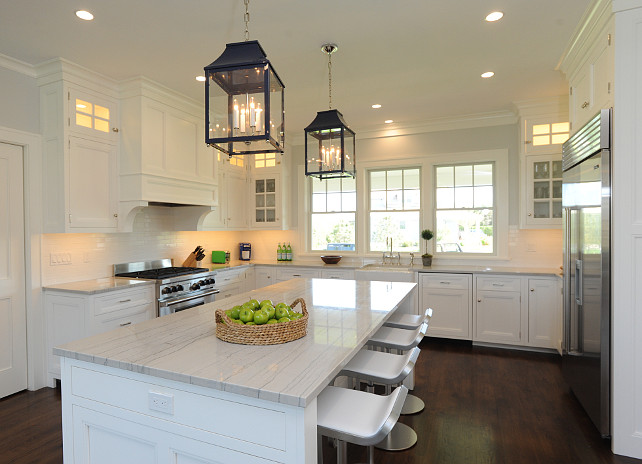 Kitchen Cottage. Cottage Kitchen Design. White Cottage Kitchen. White coastal kitchen Ideas. Stunning U-shaped kitchen with white cabinetry accented with brushed nickel hardware alongside white quartzite countertops with a subway tiled backsplash. The kitchen features a stainless steel stove below a white paneled stove hood accented with corbels across from a stainless steel industrial style, built-in refrigerator. A farm sink stands below three sash windows opposite an extra long kitchen island lined with Piston Barstools illuminated by a pair of lacquered navy lantern pendants from Oomph. Nina Liddle Design.