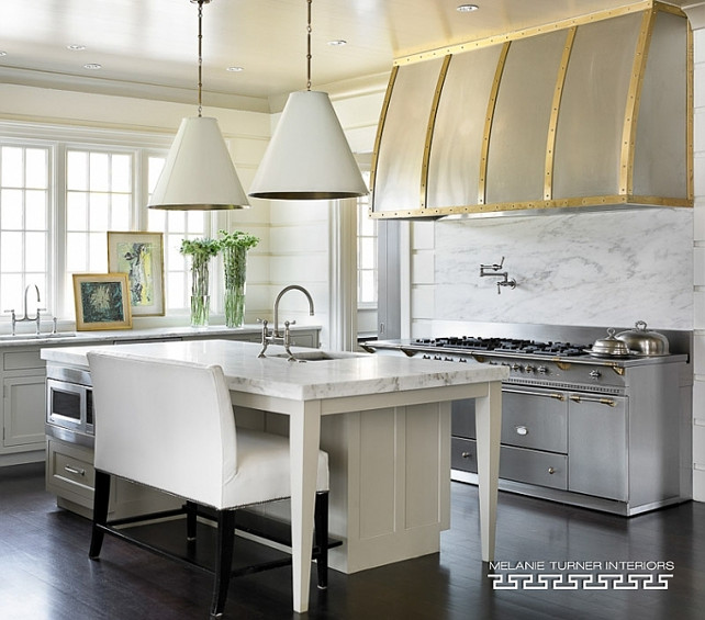 Transitional Industrial Kitchen. Transitional kitchen with kitchen features light gray cabinets paired with honed white marble countertops and a white tongue and groove backsplash and Two Goodman Hanging Lamps. #Transitional #KItchen #Industrial Melanie Turner Interiors.