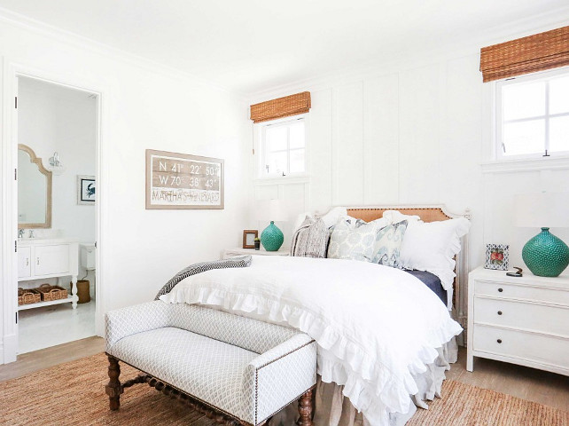 White coastal bedroom. White coastal bedroom with settee at the feet of the bed, linen bed, white nightstands, jute rug, hardwood floors, batten and board accent wall and bamboo shades. #CoastalBedroom #WhiteCoastalBedroom #CoastalInteriors