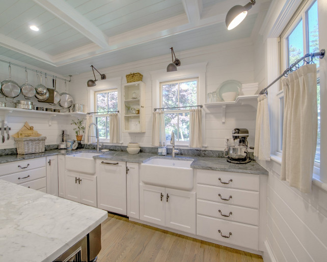 Two Farmhouse Sinks. Kitchen with Two Farmhouse Sinks. A touch of farmhouse! The kitchen features two farmhouse sinks, tongue and groove walls, open shelves, swing arm sconces, coffered ceiling with shiplap painted in light blue and a side window with lower half curtain in linen. #kitchen #Twofarmhousesinks #Kitchensinks