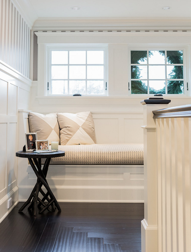 Staircase window seat - reading nook. Staircase reading nook. Staircase landing features a built-in reading nook topped with white and beige triangle pillows under windows framed by white and silver stripe wallpaper on upper walls and board and batten on lower walls alongside a branch accent table atop concentric wood floors. #Staircase #ReadingNook #WindowSeat Brookes and Hill Custom Builders.