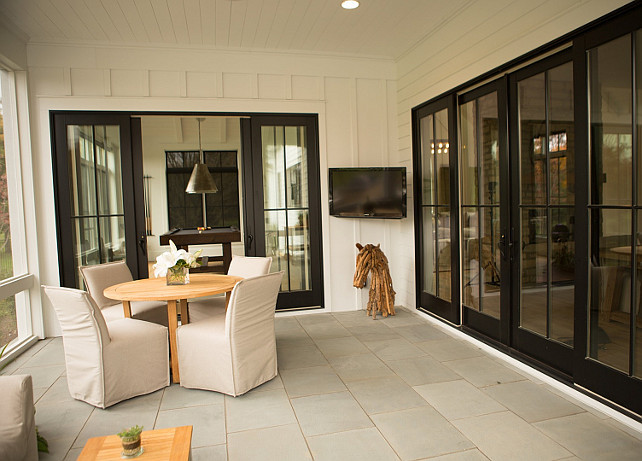 Sliding Doors to Screened in Porch.  Black Glass sliding doors open to a screened in porch filled with a round teak dining table lined with slipcovered slipper dining chairs facing a corner flatscreen TV. Hahn Builders.