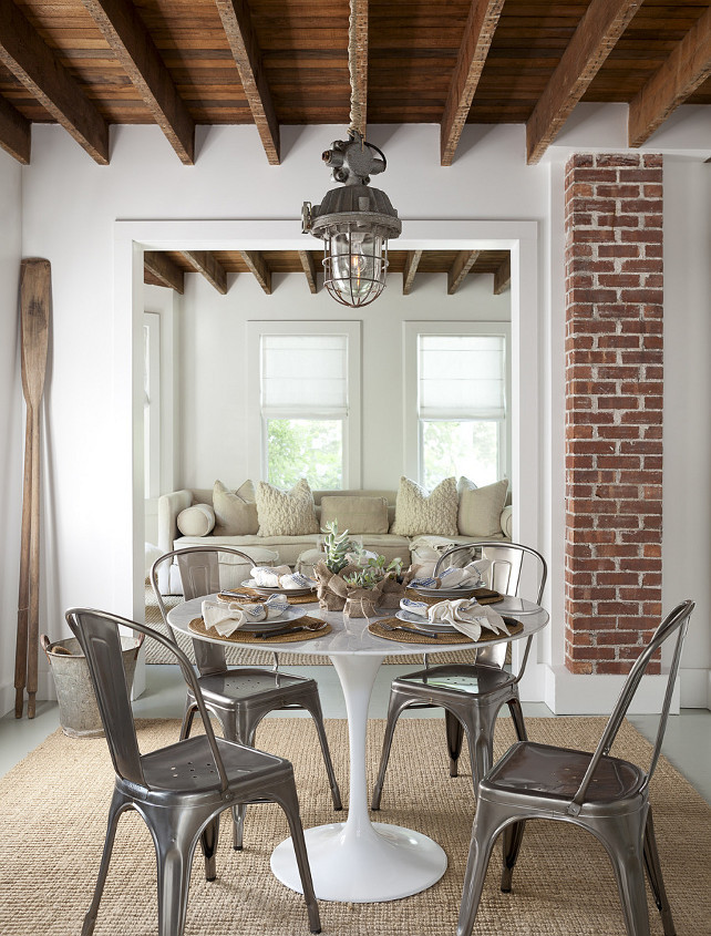 Dining Room. Transitional Dining Room. Cottage dining room. Cottage dining nook features rustic wood beams adorned with a vintage lantern over a Saarinen Dining Table surrounded by Tolix Chairs atop a jute rug.