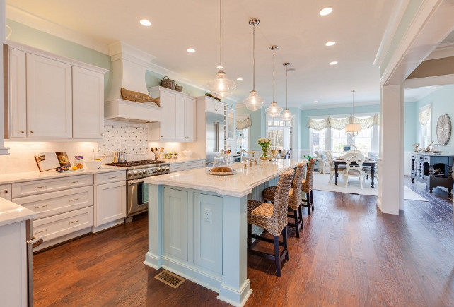 Blue Kitchen with white cabinets. The kitchen is made bright with on-trend clear glass pendants from the Progress Lighting Academy collection. The simple school house shape adds to the kitchen's simple chic appeal.